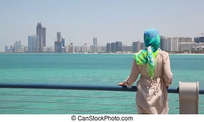 woman stand on shore and looks at skyscrapers in Abu Dhabi,...