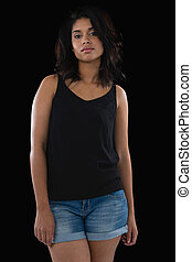Young woman standing against black background