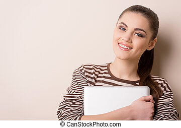 young woman standing and holding laptop. Happy young girl with her laptop, isolated on white.