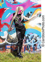 young woman standing at graffitti wall