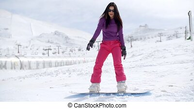 Young woman standing balancing on a snowboard in a fresh...