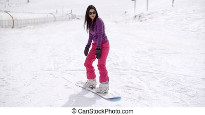 Young woman standing balancing on a snowboard