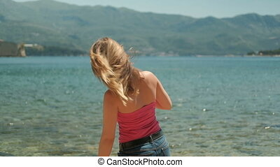 Young woman standing by shore in warm weather.
