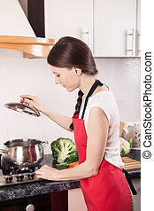 Young woman standing by the stove