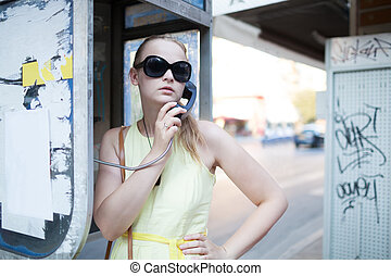 Young woman standing chatting on a public phone