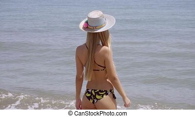 Young woman standing gazing out over the ocean - Young woman...
