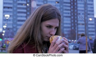 Young woman standing in an urban street and eating burger....