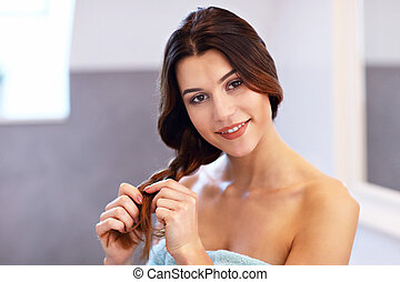 Young woman standing in bathroom and brushing hair