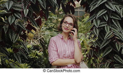 Beautiful young woman standing in botanical garden, looking at camera.
