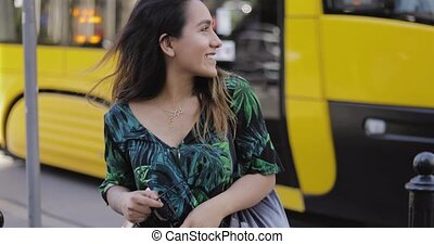 Young woman standing in front of a street tram looking at...