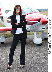 Young woman standing in front of an airplane