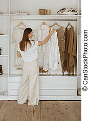 Young woman standing in front of her closet.