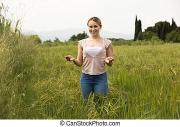 Portrait of cheerful young woman standing in green wheat field.