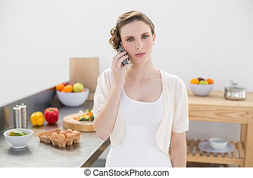 Young woman standing in kitchen while phoning