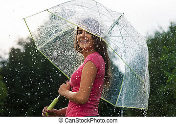 Young woman standing in summer rain with umbrella