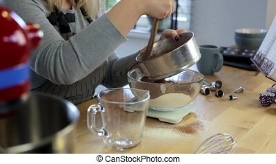 Young woman standing in the kitchen and sifting cocoa in the bowl with flour. Blonde female weighing the ingredients.