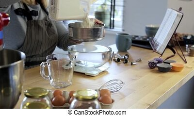 Young woman standing in the kitchen and sifting flour in the bowl. Blonde female weighing the ingredients for cooking.