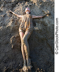 Young woman standing in the mud