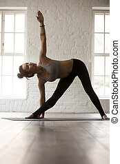 Young woman standing in Utthita Trikonasana pose, white loft stu