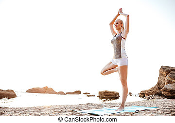 Young woman standing in yoga pose on one leg - Portrait of a...