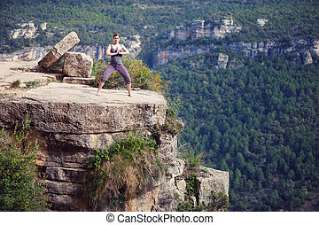 Young woman standing in yoga pose on top of cliff