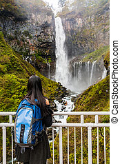 Young woman standing look at and enjoying view of nature at Kegon Falls in autumn at the Nikko National Park, Japan.
