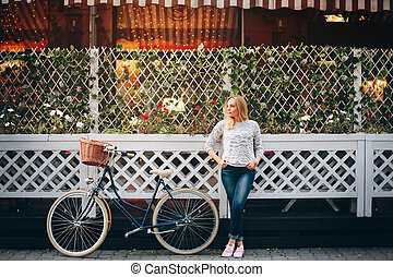 Young woman standing near cafe and waiting