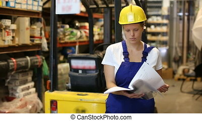Young woman standing near racks in build store bebore buying tools, holding notebook