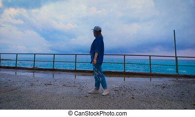 Young woman standing near the big wave on the pier, autumn...