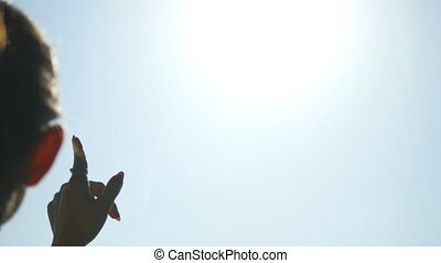 Young woman standing near the window at airport terminal and pointing to airplane in the sky. Close up