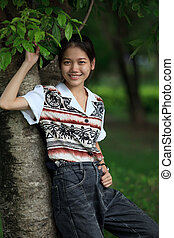 young woman standing near tree in t