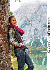 Young woman standing near tree on lake braies in south tyrol, it