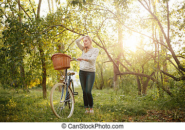 Woman Standing near Vintage Bicycle
