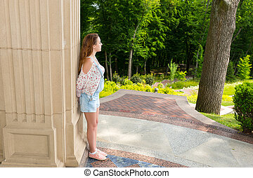 Young woman standing near wall