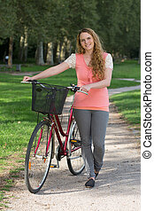 Young woman standing next to her bike