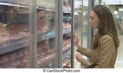 Young woman standing next to shelf with meat in the...