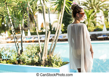 Young woman standing next to the pool