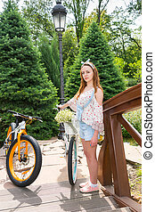 Young woman standing on a footbridge near her bicycles