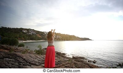 Young woman standing on a rock beach and rises hands. Flying...