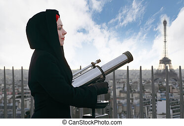 young woman standing on Arc de Triomphe with large pair of binoculars, Eiffel Tower