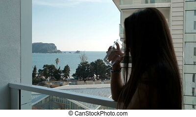 Young woman standing on balcony and drinking water outside.