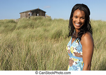 Young Woman Standing On Beach Amongst Dunes With Beach Hut...