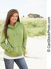 Young Woman Standing On Beach Wearing Hooded Top With Old Beach Hut In Distance