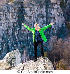 Young woman standing on cliff edge with raised hands