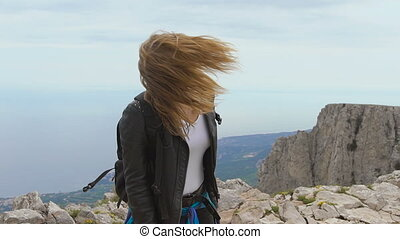 Young woman standing on cliff. She travels alone, and...