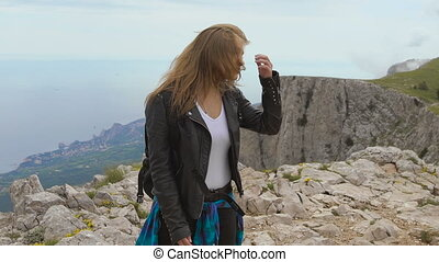 Young woman standing on cliff.