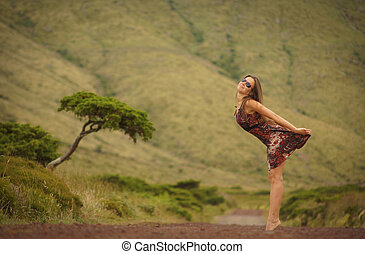 Young woman standing on country road, arching her back. View from side