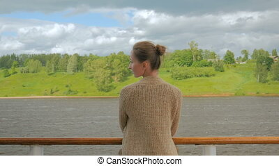 Young woman standing on deck of cruise ship and looking at river and landscape