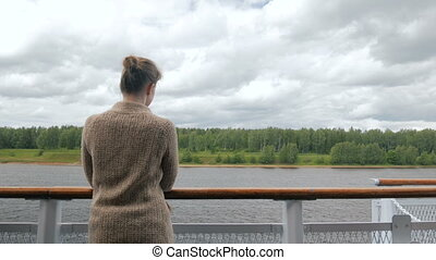 Young woman standing on deck of cruise ship and looking at...