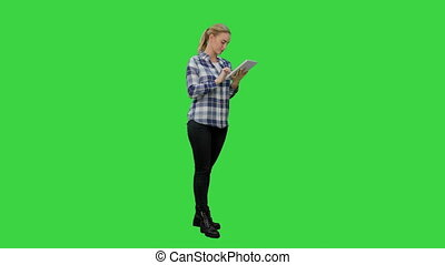 Young woman standing on green background with digital tablet on a Green Screen, Chroma Key.
